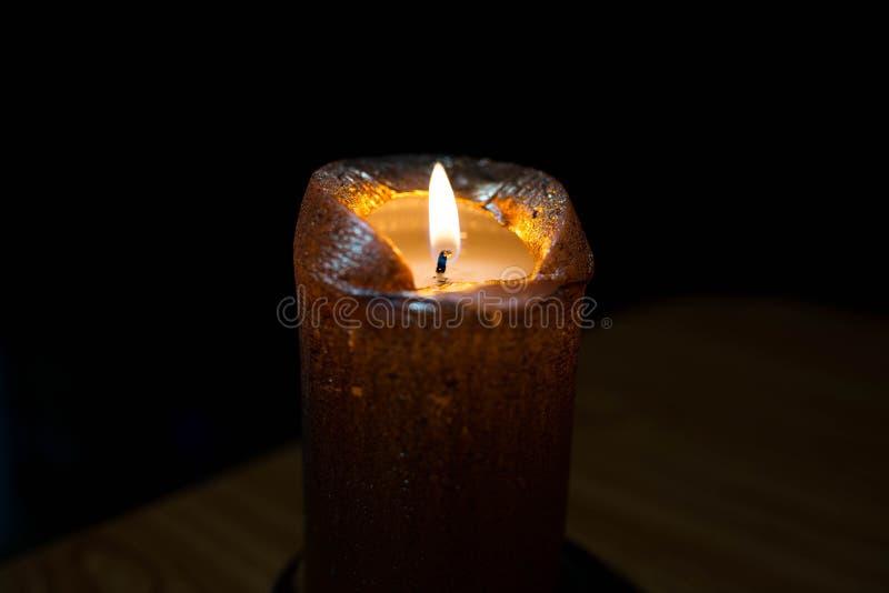 Luz dourada de queimadura da vela no foco em uma sala escura fotografia de stock