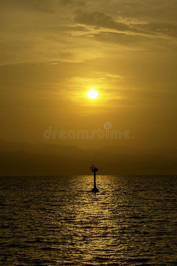 Luz dourada do nascer do sol atrás das montanhas e a sombra da lâmpada de sinal para navegar no mar imagens de stock