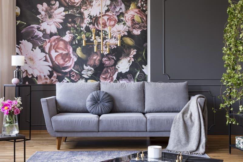 Luz dourada industrial do pendente e mobília preta em um interior escuro da sala de visitas com papel de parede floral e um sofá  imagem de stock