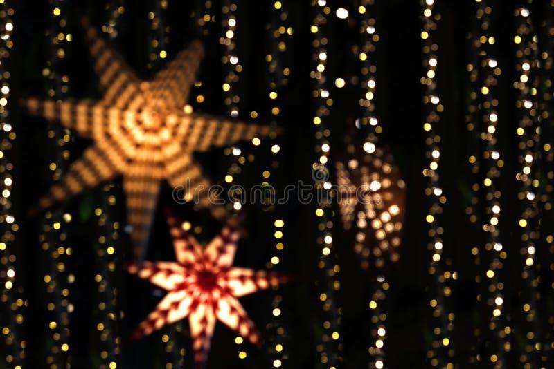 A luz e a estrela borradas do bokeh para o Natal da decoração, o Natal e luzes decorativas do ano novo brilham a faísca para o fu fotografia de stock