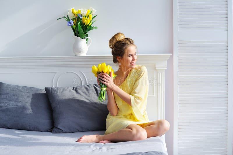 Luz e mulher da manhã com tulipas amarelas imagens de stock