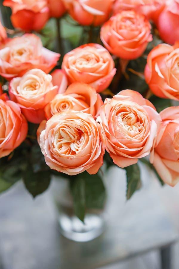 Luz - flores cor-de-rosa das rosas do arbusto do pêssego do nd no vaso na tabela de madeira Ramalhete bonito do verão Arranjo com fotografia de stock royalty free