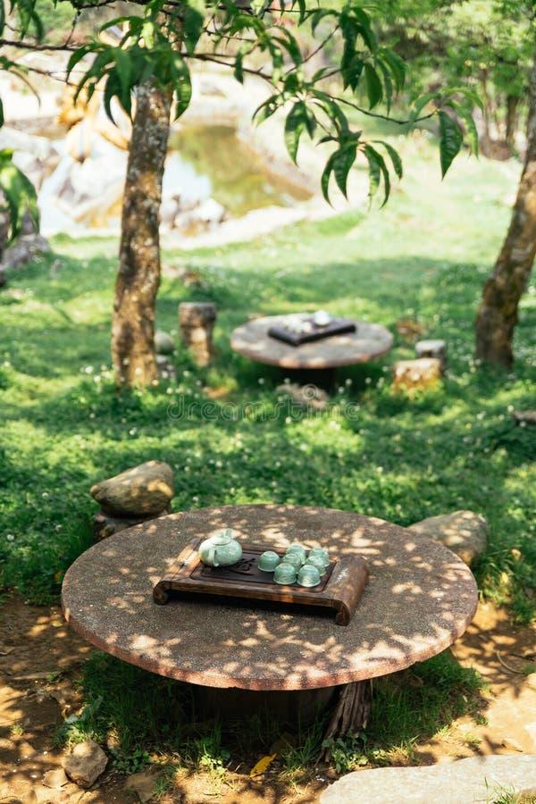 Luz - grupo de chá cerâmico verde que inclui o frasco, os copos e a placa na tabela de pedra sob a sombra da árvore em Ham Rong M fotografia de stock