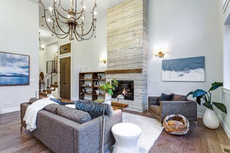 Luz increíble y sala de estar airosa con el alto techo en un hogar de la nueva construcción fotografía de archivo