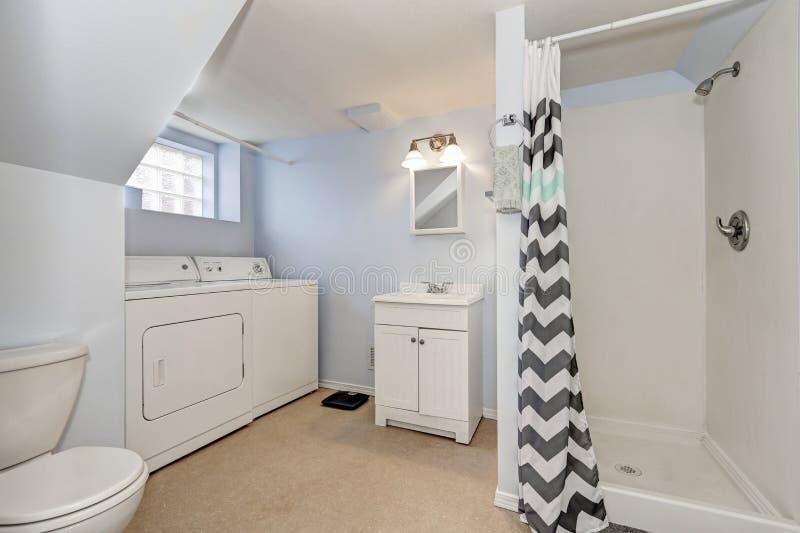 Luz - interior azul do banheiro com dispositivos da lavanderia imagens de stock