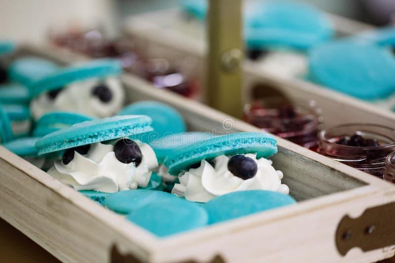 Luz - macarons azuis de turquesa enchidos com o chantiliy, barra de chocolate do casamento imagem de stock royalty free