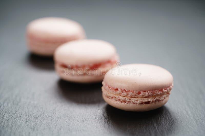 Luz - macarons cor-de-rosa no fundo da ardósia imagens de stock