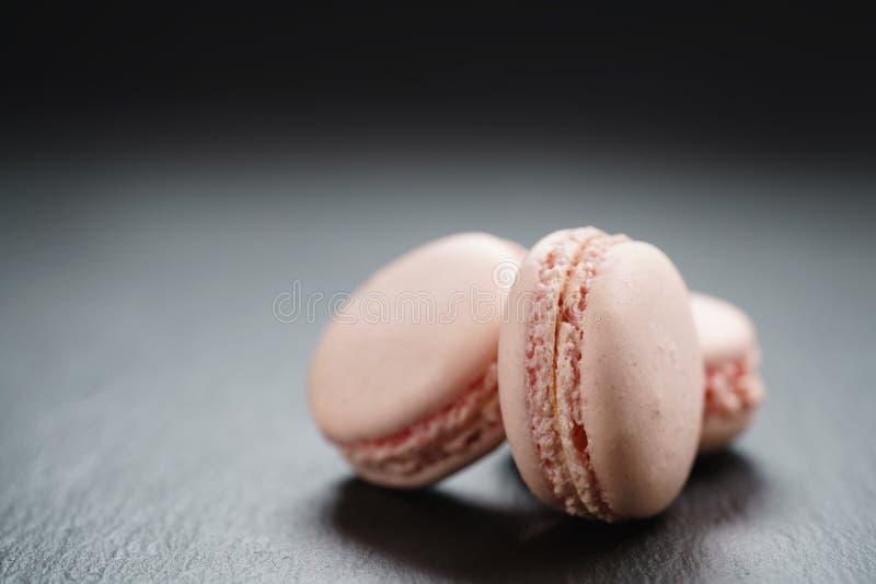 Luz - macarons cor-de-rosa no fundo da ardósia com espaço da cópia imagem de stock royalty free