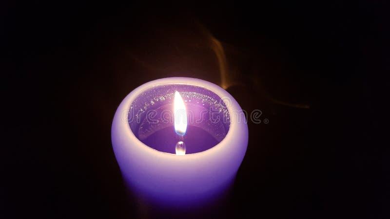 Luz minúscula da vela roxa na escuridão fotos de stock royalty free