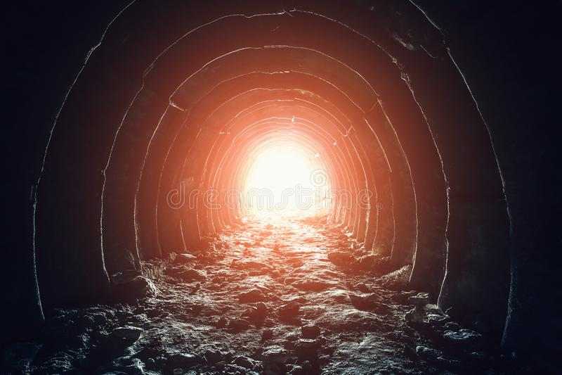 Luz misteriosa na extremidade do túnel Escape e retire à liberdade e espere o conceito Corredor industrial abandonado na mina do  imagens de stock