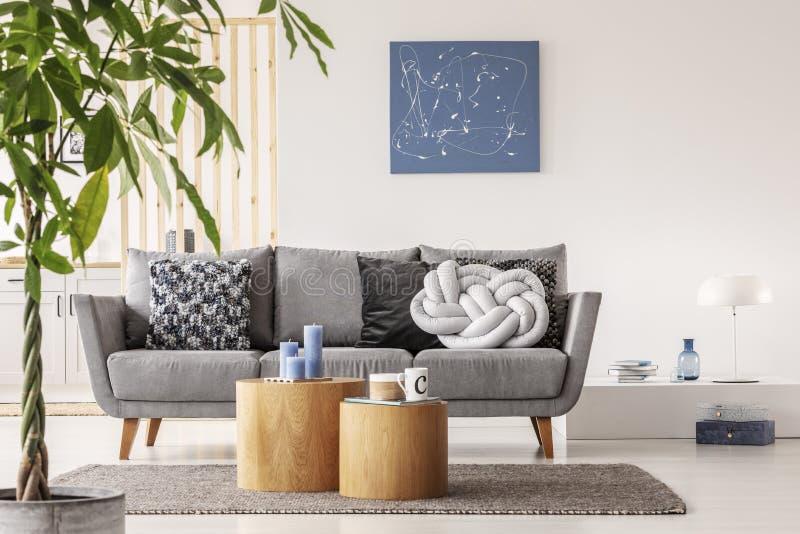 Luz na moda do nó - descanso cinzento no sofá escandinavo confortável foto de stock