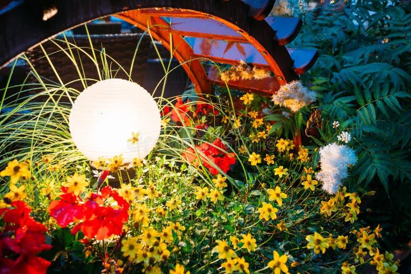 Luz pequena decorativa do jardim, lanternas na cama de flor em F verde imagens de stock royalty free