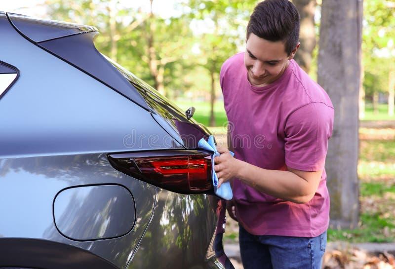 Luz posterior del coche del hombre que se lava joven con el trapo imagen de archivo