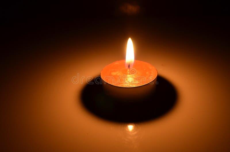 Luz roja de la vela con la sombra y la reflexión fotos de archivo libres de regalías