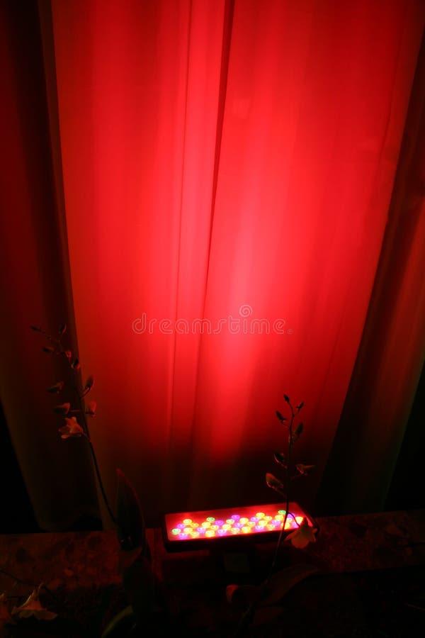 Luz roja del punto contra la cortina fotografía de archivo libre de regalías