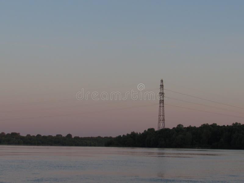 Luz rosácea del cielo gris de la costa del amanecer en un río de la ciudad con un paisaje con una torre negra foto de archivo libre de regalías