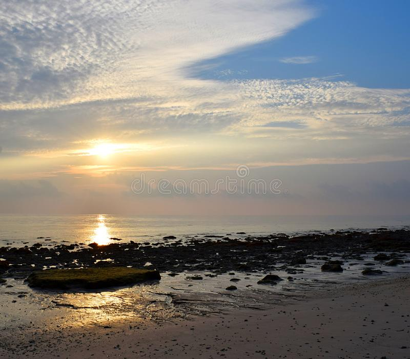 Luz solar amarela dourada brilhante com teste padrão das nuvens brancas no céu da manhã na praia rochoso - fundo natural foto de stock royalty free