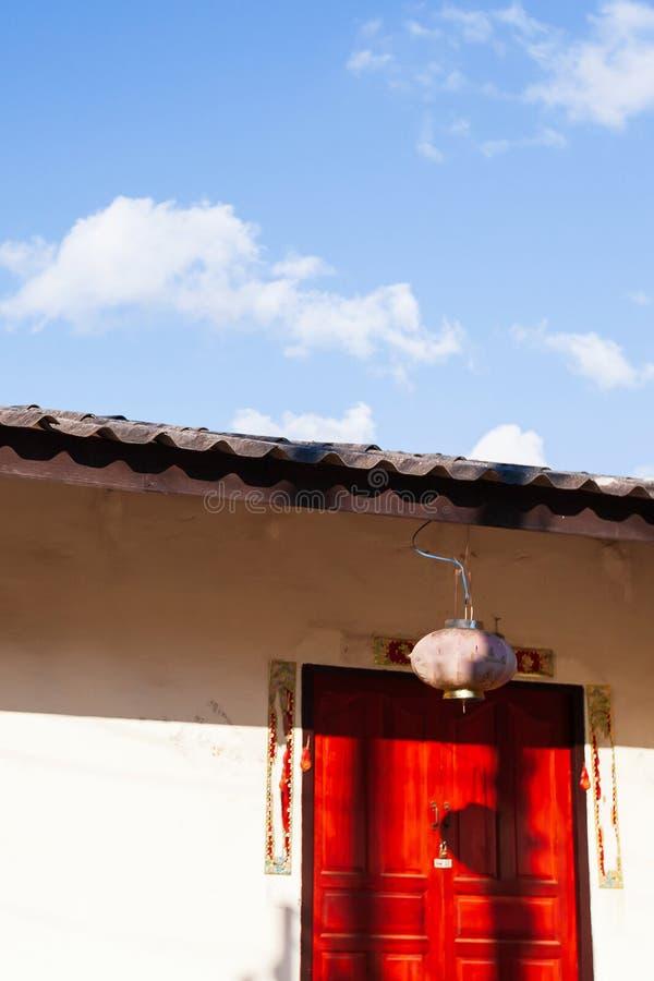 Luz solar brilhante que brilha em uma casa yunnanese velha, em umas cores bonitas da porta vermelha, em um céu azul e em uma somb fotografia de stock royalty free