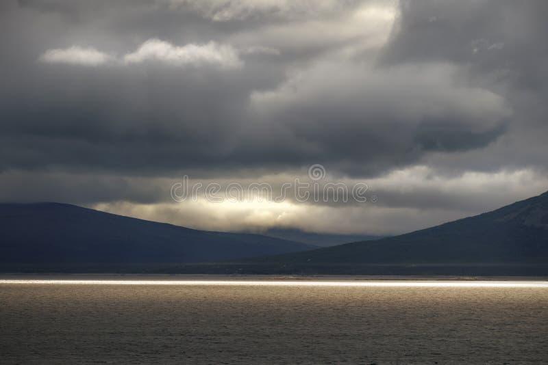 Luz solar colorida dourada na hora dourada no grande lago com fundo dramático e temperamental da paisagem fotos de stock