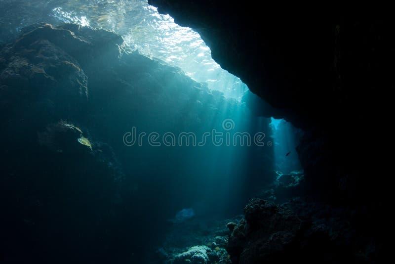 A luz solar desce na caverna escura, submersa fotografia de stock royalty free