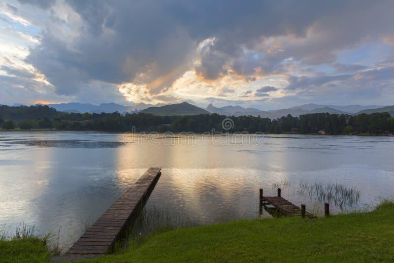 A luz solar e as nuvens refletem na água foto de stock