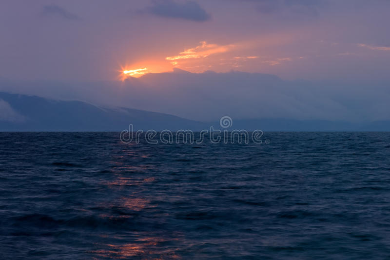 A luz solar mágica na obscuridade nubla-se sobre o lago ondulado de Sevan imagem de stock royalty free