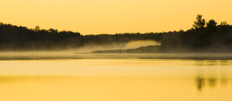Luz solar na névoa e na água fotografia de stock royalty free