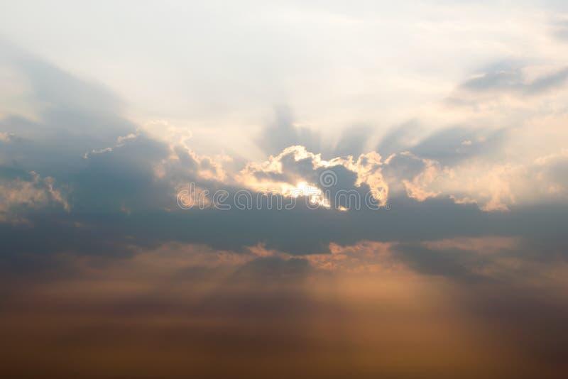 Luz solar que penetra através das nuvens durante o por do sol imagens de stock