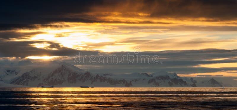 Luz a través de las nubes sobre las montañas nevadas, península antártica de la puesta del sol foto de archivo
