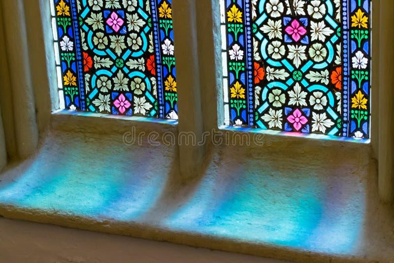 Luz a través del vidrio coloreado en ventana en iglesia vieja imagen de archivo