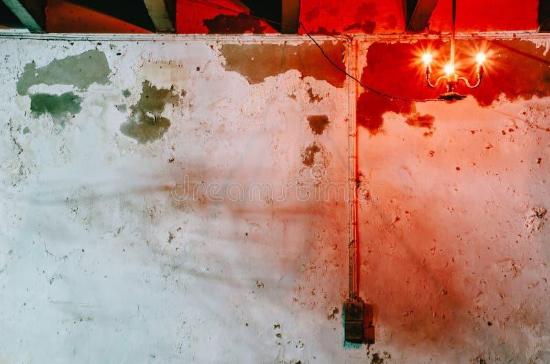 A luz vermelha da lâmpada preta estava pendurando na parede suja branca velha que tem a mancha preta no espaço da noite e da cópi imagens de stock royalty free