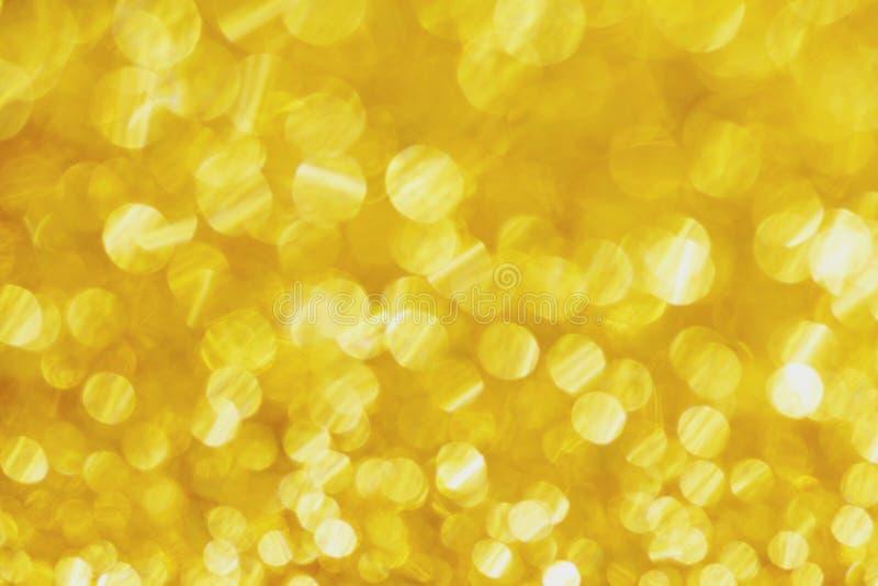 Luzes abstratas do bokeh do defocus no fundo dourado imagem de stock