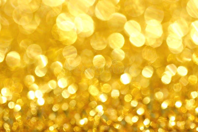 Luzes abstratas do bokeh do defocus no fundo dourado fotografia de stock