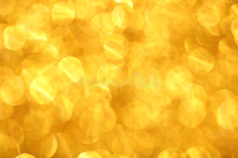 Luzes abstratas do bokeh do defocus no fundo dourado imagens de stock royalty free