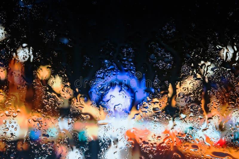 Luzes atrás das gotas da água perto acima na cidade da rua imagem de stock royalty free