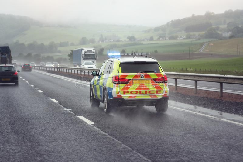 Luzes azuis de piscamento da sirene de polícia na estrada em condições de mau tempo fotos de stock royalty free