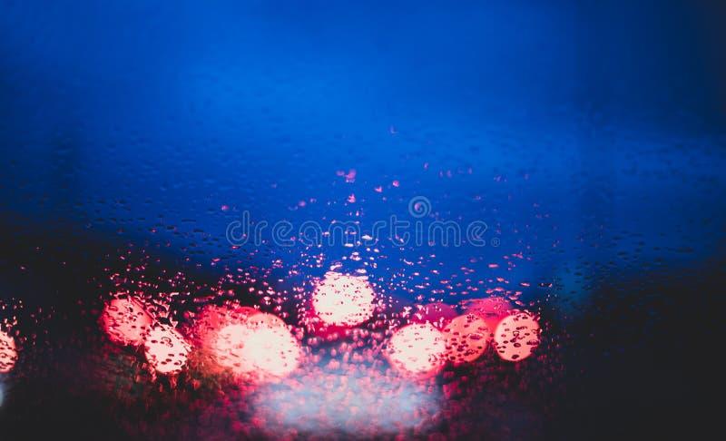 Luzes borradas dos carros do interior de um carro com gotas na janela imagens de stock royalty free