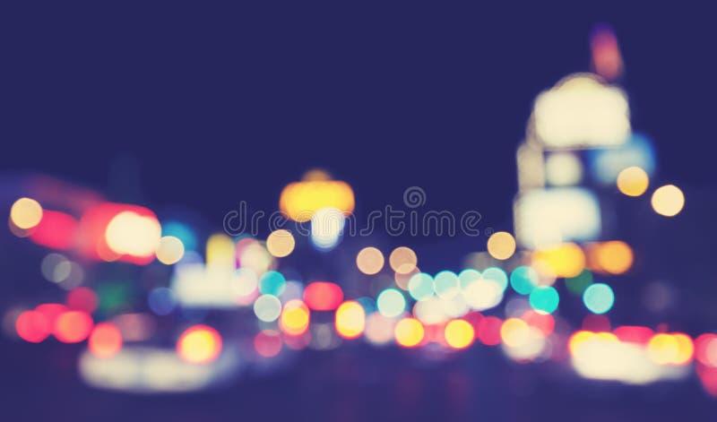 Luzes borradas tonificadas vintage da cidade na noite foto de stock royalty free