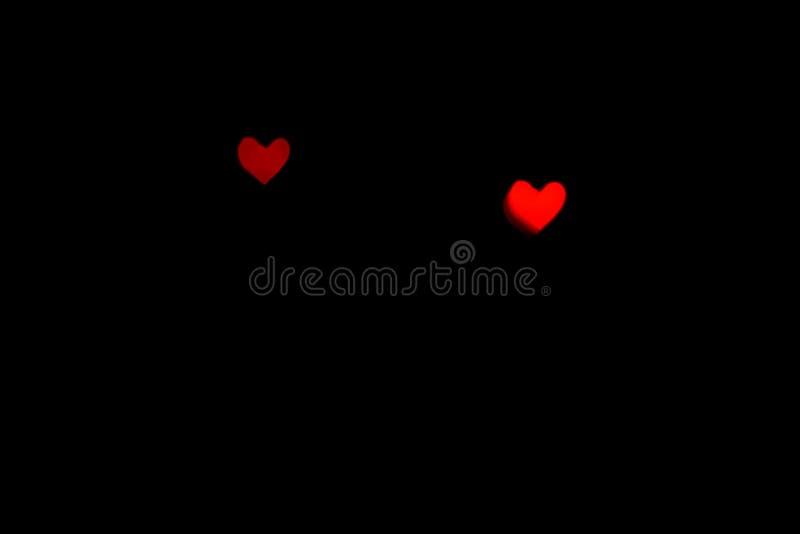 Luzes borradas vermelhas na forma dos corações na obscuridade ilustração royalty free