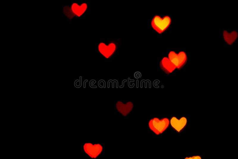 Luzes borradas vermelhas na forma dos corações na obscuridade ilustração stock