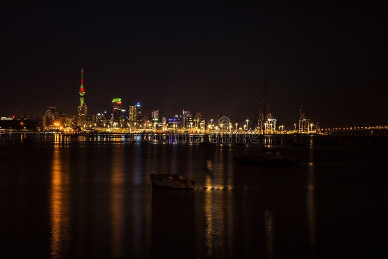 Luzes brilhantes da baixa da cidade de Auckland e do porto refletido na ba?a de Okahu com um bote no primeiro plano macio imagens de stock royalty free