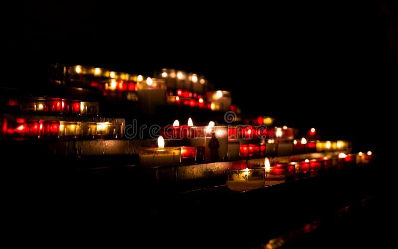 Luzes brilhantes de velas ardentes na escuridão da igreja imagem de stock royalty free