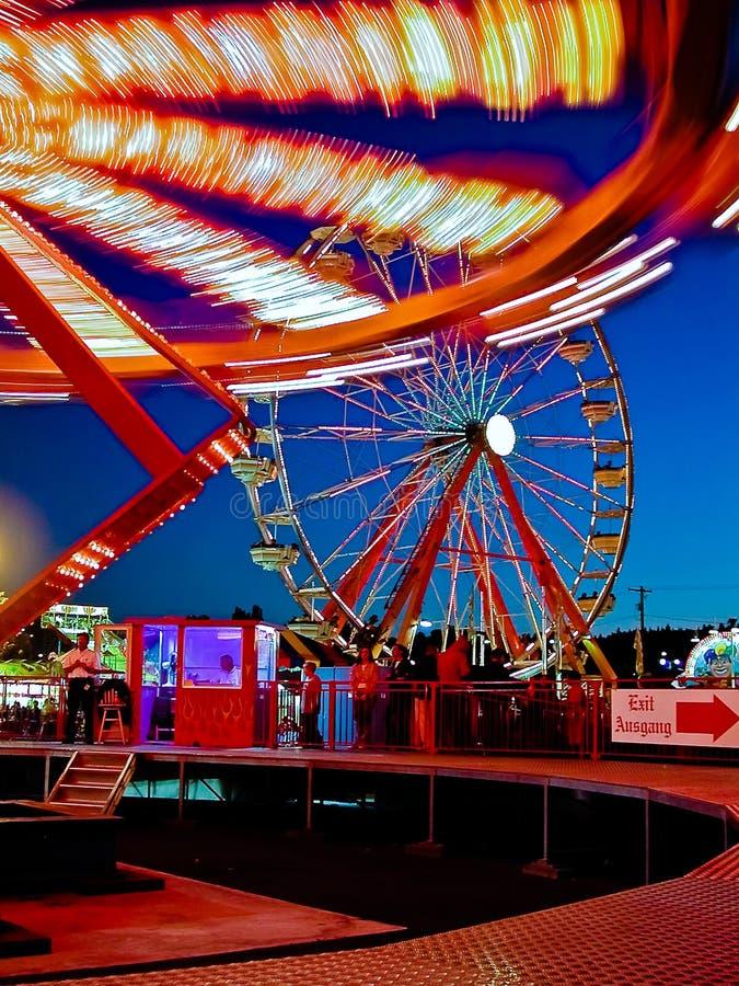 Luzes brilhantes em passeios no parque de diversões imagens de stock