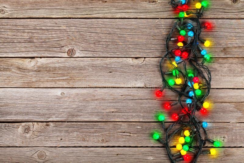 Luzes coloridas do Natal sobre o fundo de madeira imagem de stock