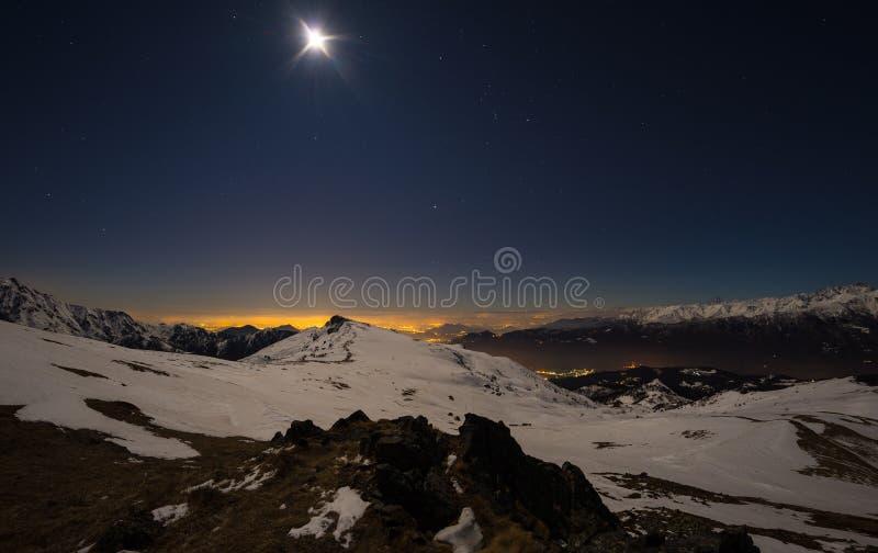 Luzes da cidade de Turin, opinião da noite dos cumes cobertos de neve pelo luar Constelação da lua e do Orion, céu claro, lente d imagem de stock