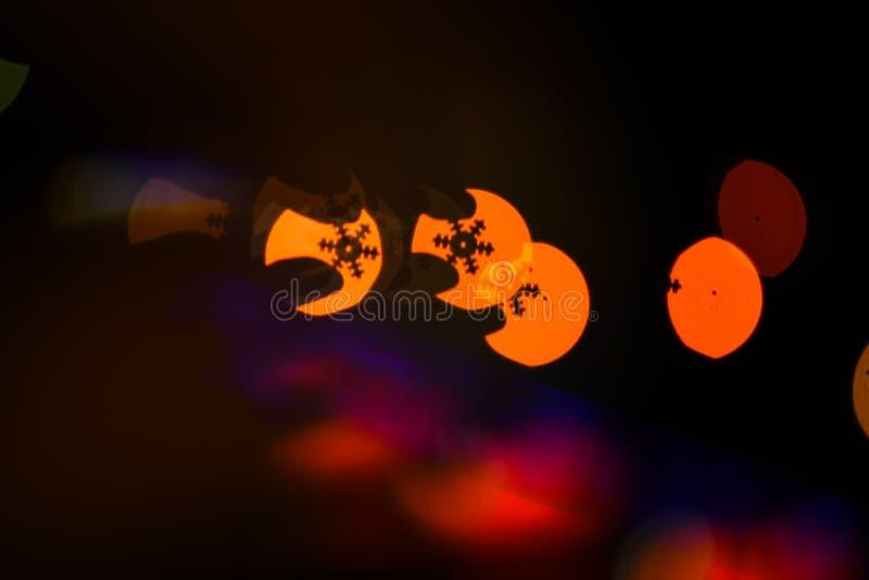 Luzes da festão do Natal borradas no fundo preto Conceito do Natal Luzes da festão colorida borradas como imagem de stock royalty free