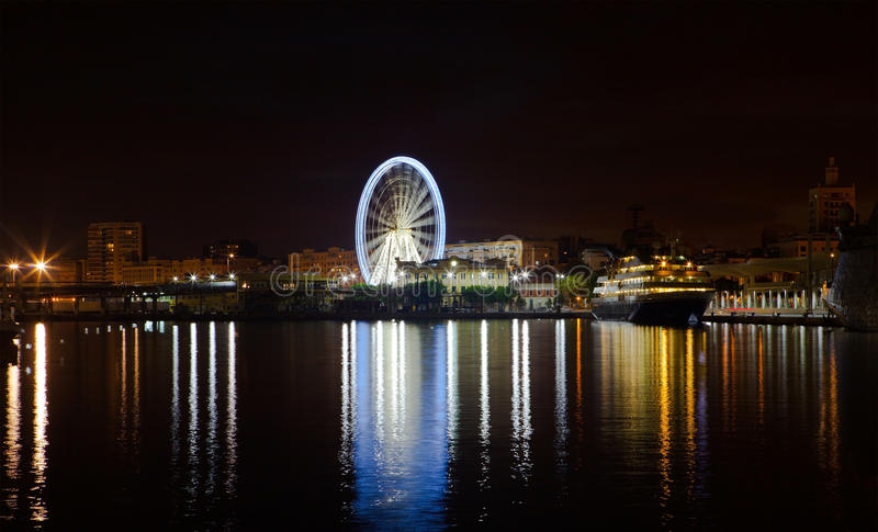 Luzes da noite no porto de Malaga Ferris roda dentro o fundo foto de stock