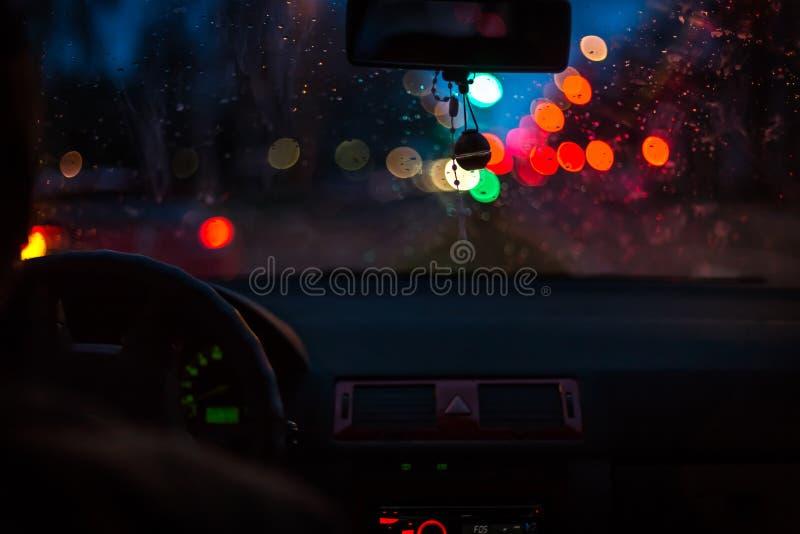 Luzes de Bokeh do tráfego no dia molhado Tempestade da noite que chove o conceito da condução de carro fotos de stock