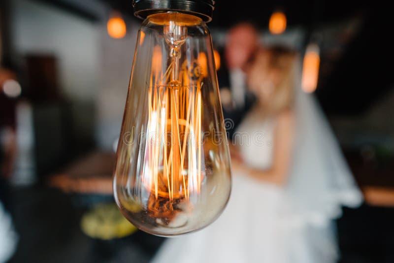 Luzes de bulbos retros os recém-casados acoplam o abraço imagem de stock