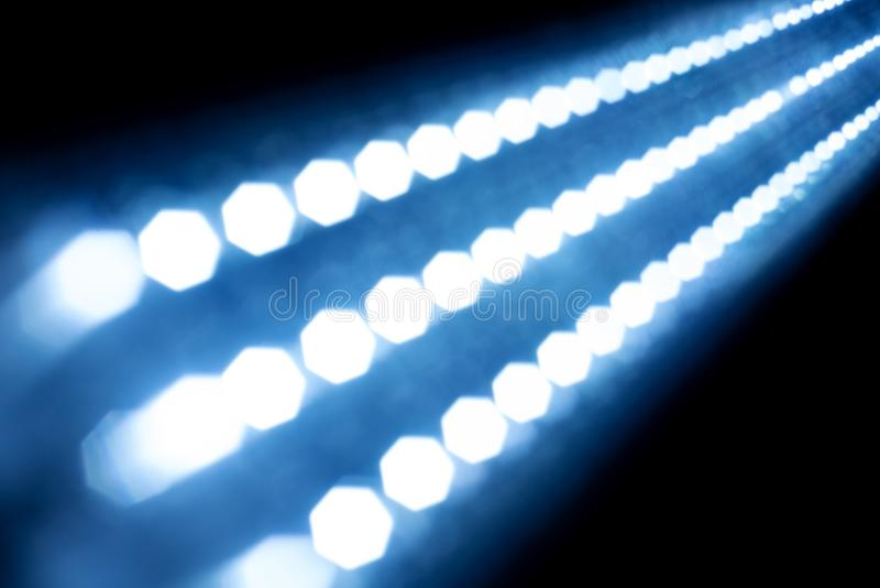 Luzes de incandescência da textura abstrata no fundo preto tira clara borrada Fulgor azul muitas ampolas de incandescência pequen fotografia de stock
